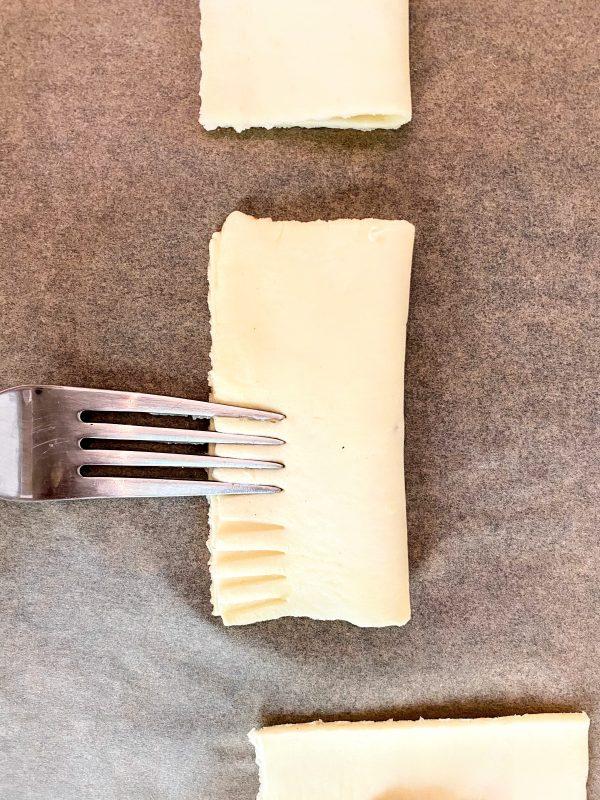 Mit einer Gabel werden die Ränder der Blätterteigravioli mit Keksteig plattgedrückt um ein schönes Muster zu erzeugen