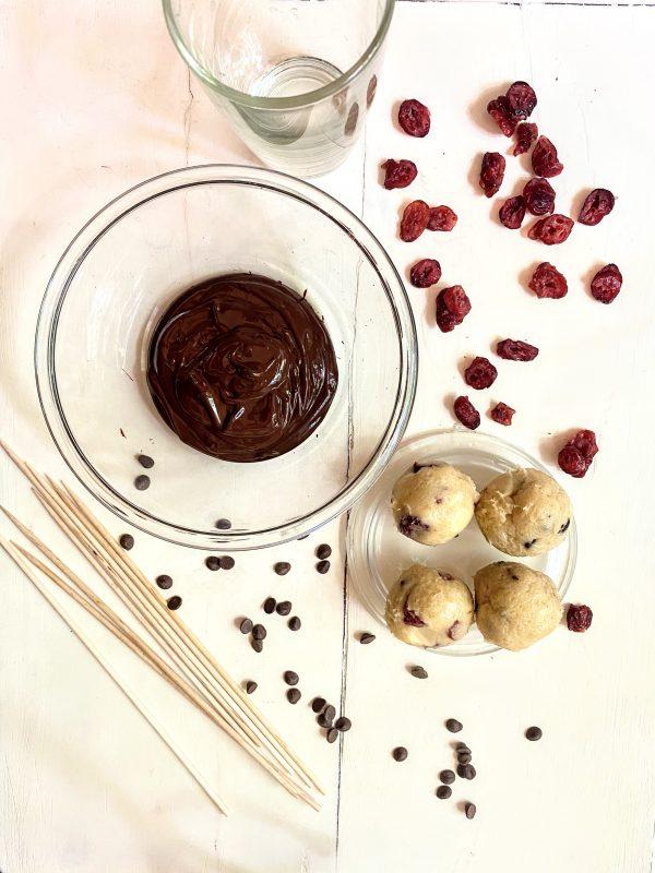 Die Zutaten für die Cake Pops liegen bereit, drumherum sind Cranberries und Schokotröpfchen verteilt