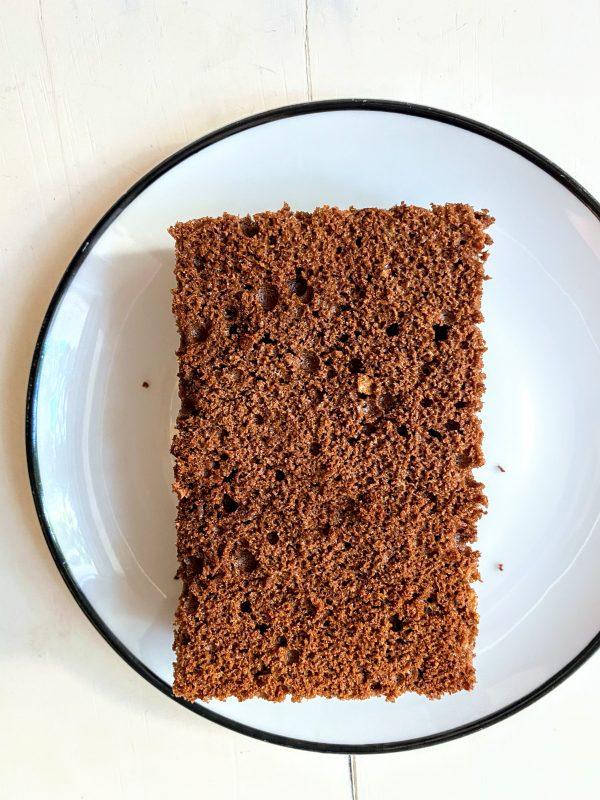Ein rechteckiges Stück Brownie liegt auf einer Kuchenplatte