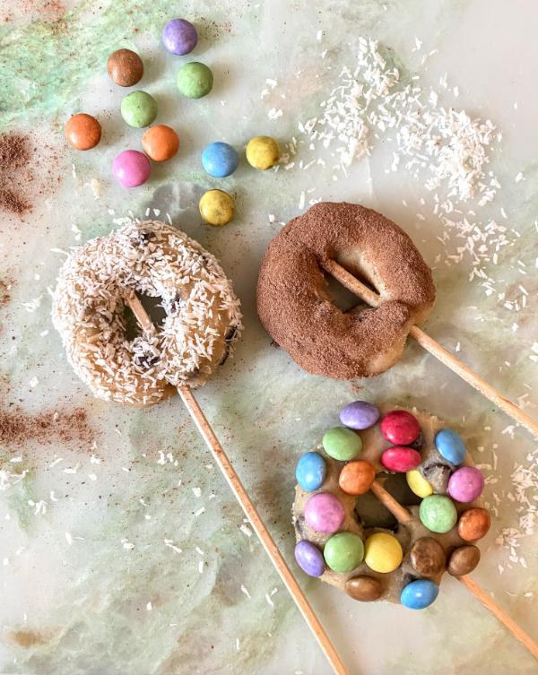 Die fertigen Cookie Dough Donuts, verziert mit Kokosraspeln, Kakaopulver und Smarties.